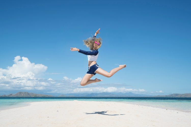 Girl jumping on beach on holiday